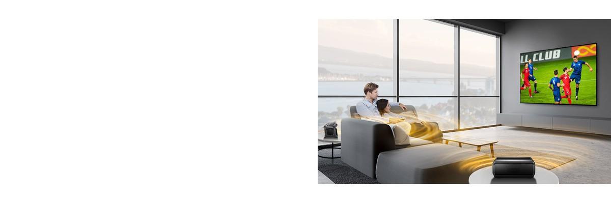 Egy férfi és egy nő sportközvetítést néz a TV-ben a nappaliban hátsó Bluetooth hangszórókkal