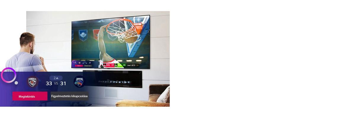 TV-képernyőn megjelenő jelenet egy kosárlabda-mérkőzésről, amint megjelenik a sportfigyelmeztetés.