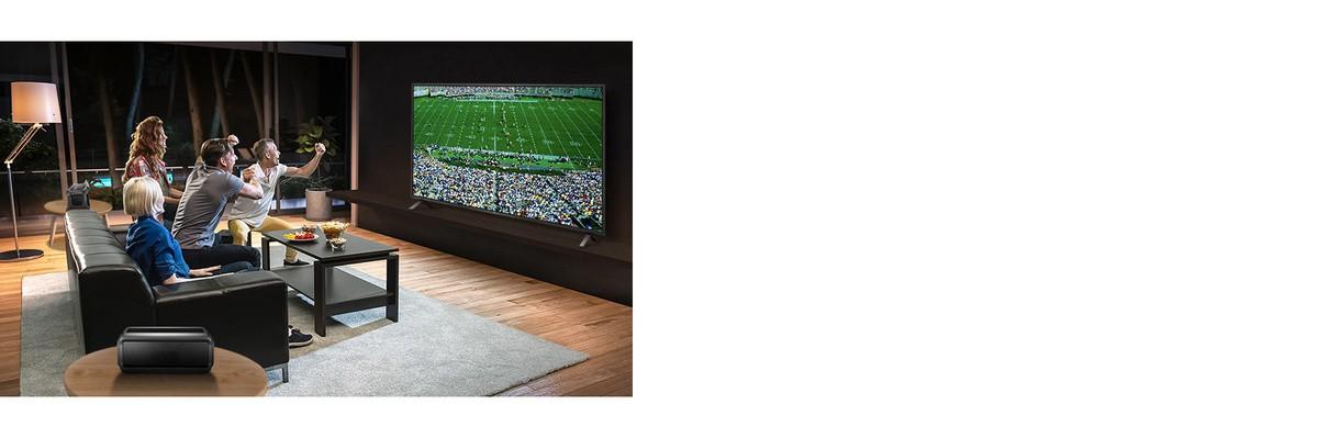Oameni care urmăresc un joc sportiv la televizor în camera de zi, cu difuzoare Bluetooth în spate.