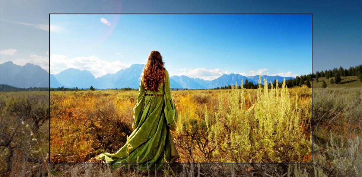 Un ecran TV care prezintă o scenă dintr-un film fantastic, cu o femeie care stă pe o câmpie, cu fata spre munti.