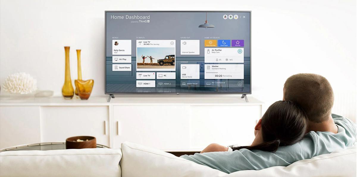 Un bărbat si o femeie care stau pe o canapea în camera de zi, cu Home Dashboard pe ecranul TV