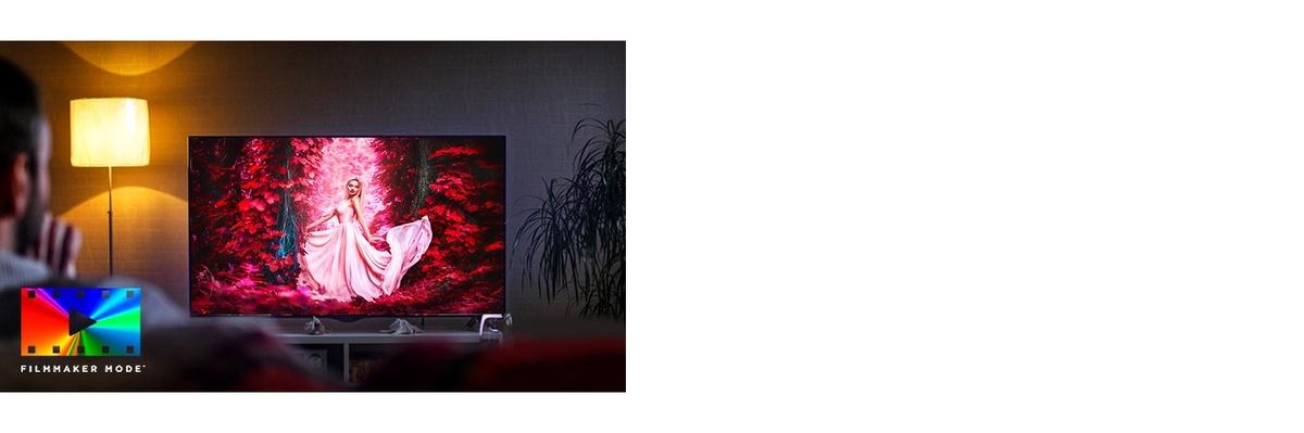 Un bărbat si o femeie care stau pe o canapea în camera de zi, cu un film plin de culoare pe ecranul TV