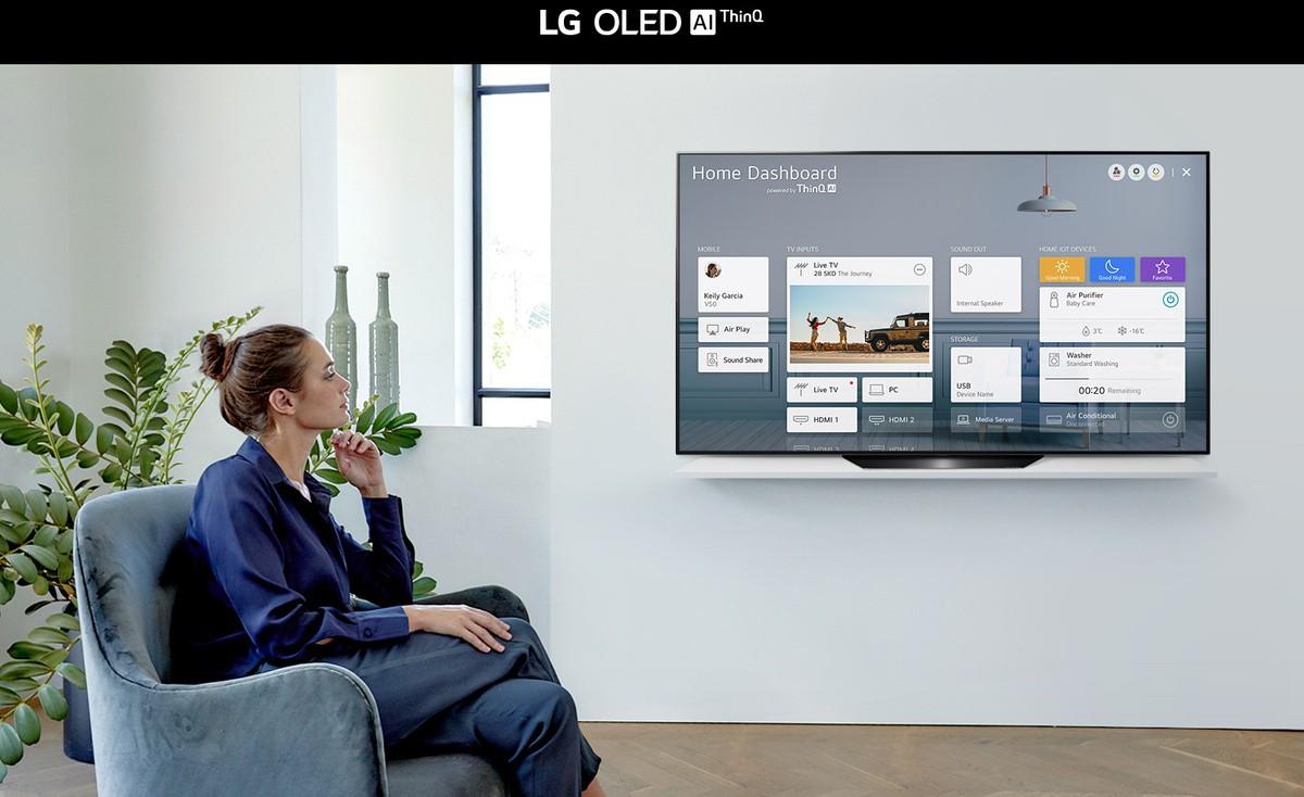 O femeie care stă pe un scaun în camera de zi, cu Home Dashboard pe ecranul TV