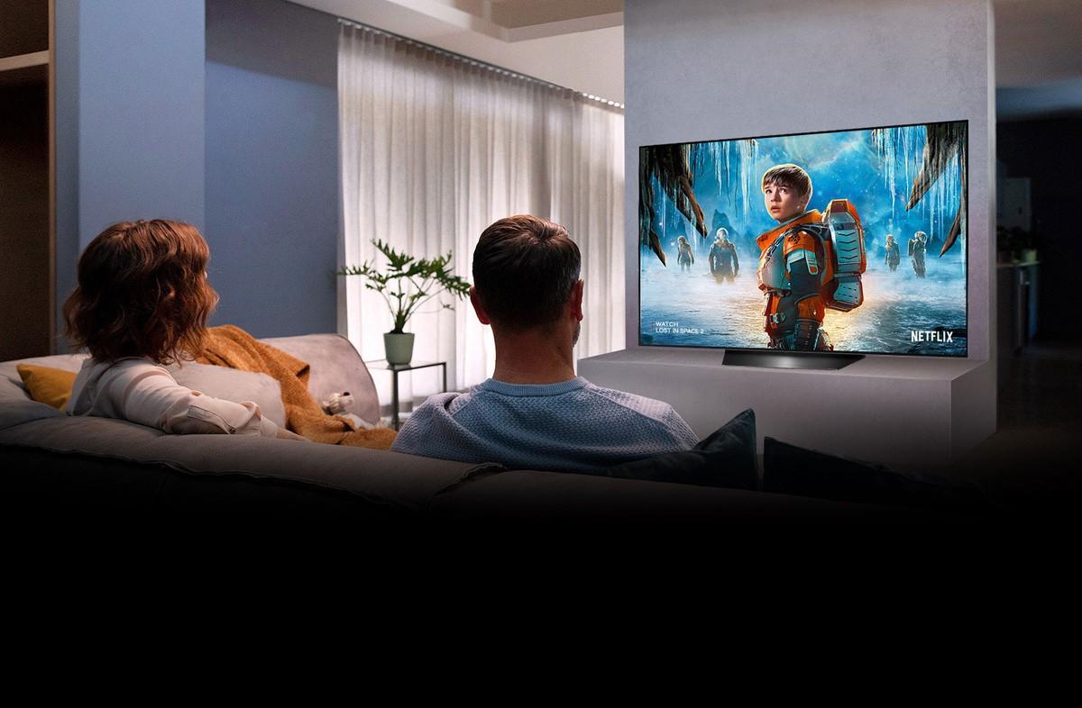 Cuplu care stă pe o canapea în camera de zi si vizionează serialul LOST IN SPACE 2 la televizor