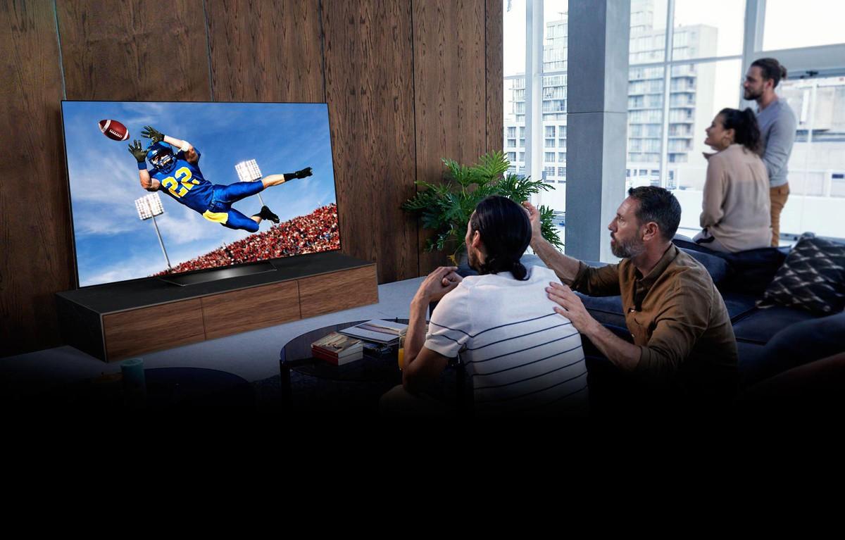 Oameni care urmăresc un meci de fotbal american la televizor, în camera de zi