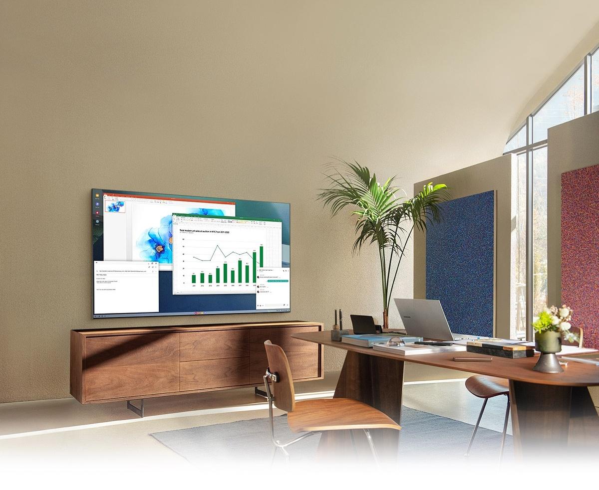 Intr-un birou la domiciliu, ecranul televizorului QLED arata functia PC pe TV care permite conectarea televizorului de acasa la computerul de birou.